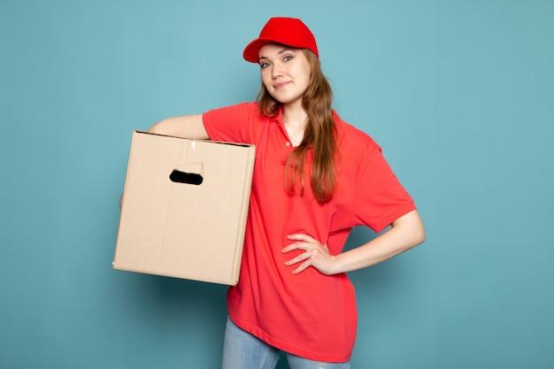 Attraktiver kurier der weiblichen vorderansicht in der roten kappe des roten poloshirts und in der jeans, die box hält, die auf dem blauen hintergrundlebensmittelservicejob aufwirft