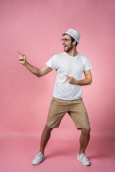Attraktiver lächelnder armfinger des jungen mannes, der zeigt, um leeren raum in gerade blick signal zu tragen tragen lässig weißes t-shirt isoliert.