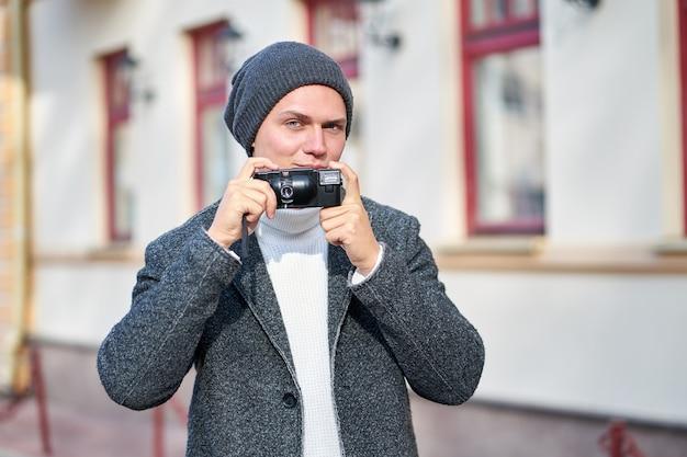 Attraktiver lächelnder hipster-trendmann, der einen grauen mantel, einen weißen pullover und einen grauen hut mit kamera trägt