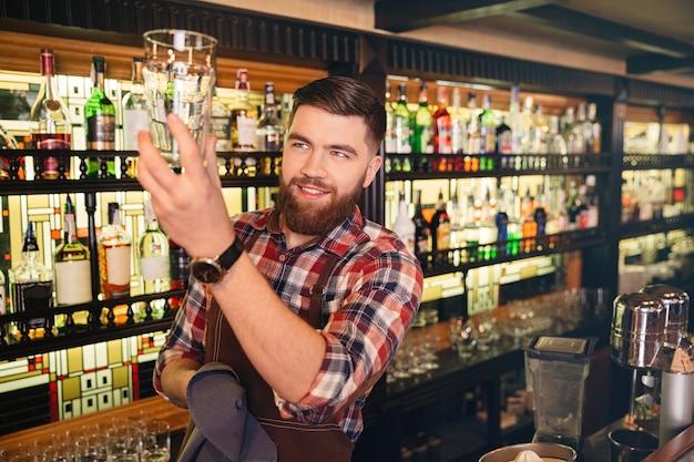 Attraktiver lächelnder junger barkeeper, der in der kneipe steht und gläser abwischt