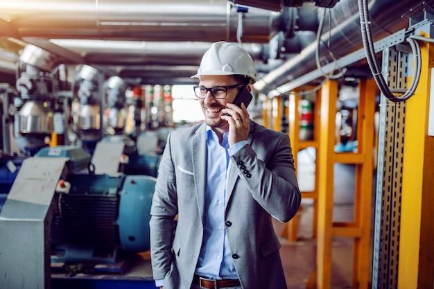 Attraktiver lächelnder kaukasischer geschäftsmann im anzug und mit dem helm auf dem kopf, der am telefon spricht, während er im kraftwerk steht.