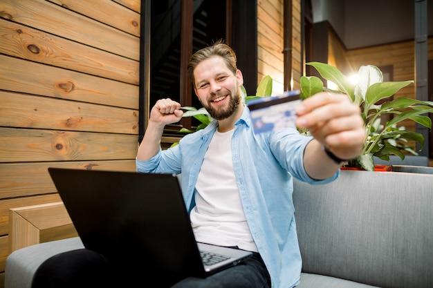 Attraktiver lächelnder kaukasischer mann, der laptop im co-arbeitsraum verwendet und kreditkarte hält
