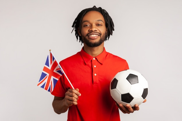 Attraktiver lächelnder mann, der britische flagge und fußballschwarzweiss-ball hält, vereinigte fußballliga.