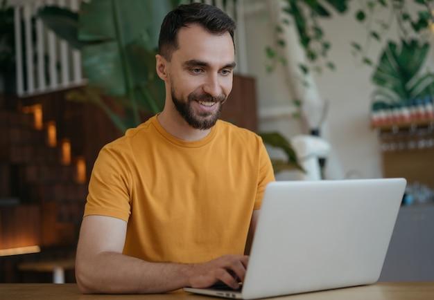 Attraktiver lächelnder mann mit laptop, der von zu hause aus arbeitet. porträt des jungen texters, der tippt