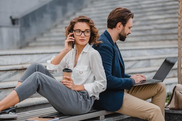 Attraktiver lächelnder mann und frau, die telefonieren, sitzen auf der treppe im städtischen stadtzentrum
