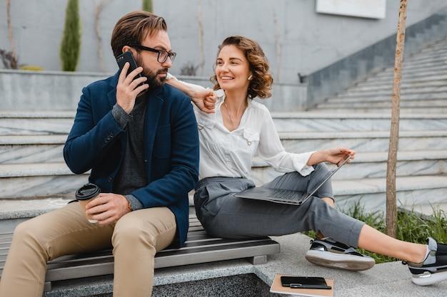 Attraktiver lächelnder mann und frau, die telefonieren, sitzen auf der treppe