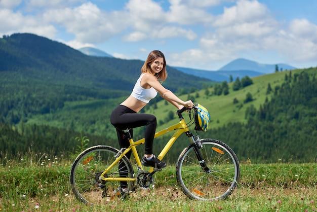 Attraktiver lächelnder weiblicher fahrer, der auf gelbem mountainbike auf einem ländlichen weg fährt