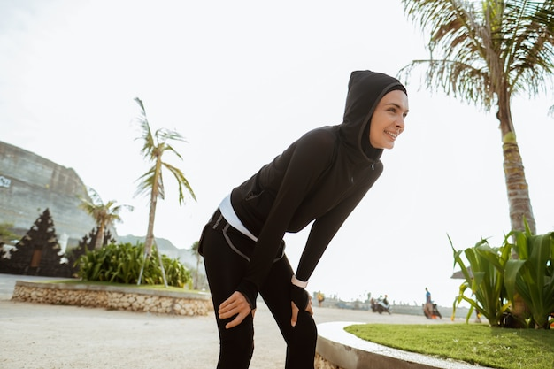 Attraktiver läufer, der nach dem joggen im freien eine pause macht