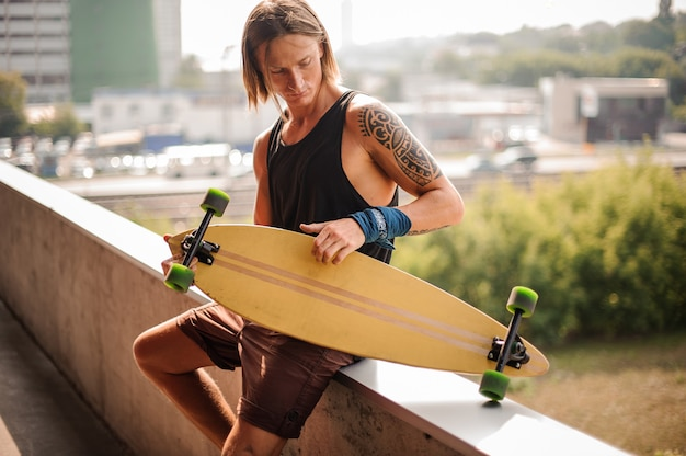 Attraktiver langhaariger kerl, der auf der brüstung mit longboard sitzt