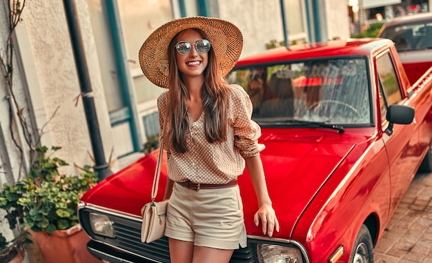 Attraktiver mädchentourist in einer bluse, einer sonnenbrille und einem strohhut steht in der nähe eines roten autos. das konzept von tourismus, reisen, freizeit.
