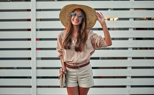Attraktiver mädchentourist in sonnenbrille, bluse und strohhut auf dem hintergrund eines weißen holzzauns. das konzept von tourismus, reisen, freizeit.