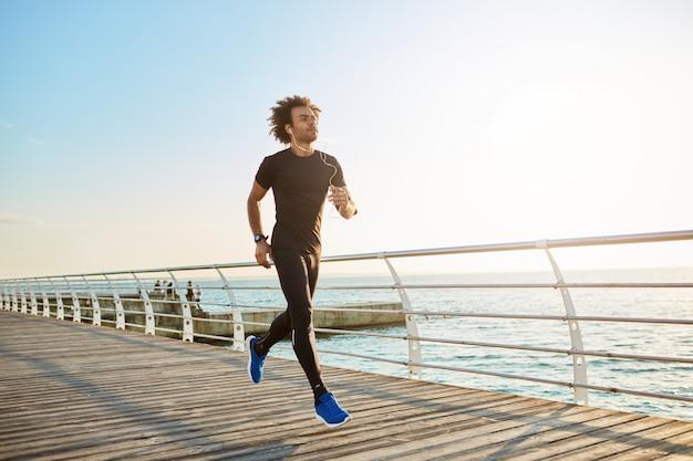 Attraktiver männlicher athlet, der stilvolle schwarze sportkleidung und blaue turnschuhe trägt. figur des mannathleten, der cardio-laufübungen am sonnigen sommermorgen tut.