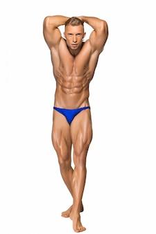 Attraktiver männlicher bodybuilder auf weißer wand