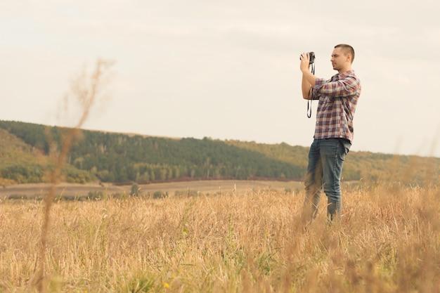 Attraktiver männlicher fotograf draußen bei sonnenuntergang