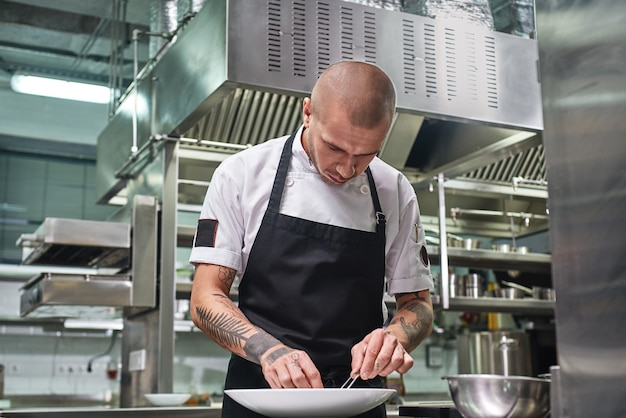 Attraktiver männlicher koch mit tattoos auf den armen, der sein gericht auf dem teller in der restaurantküche garniert