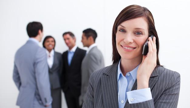 Attraktiver manager am telefon mit ihrem team im hintergrund