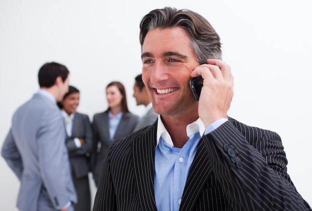 Attraktiver manager am telefon mit seinem team im hintergrund