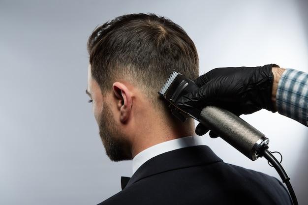 Attraktiver mann am friseursalon, der nach unten schaut, die hände des mannes, die hemd tragen, das einen haarschnitt für mann mit schwarzen haaren am studiohintergrund, porträt macht.