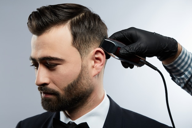 Attraktiver mann am friseursalon, der nach unten schaut, die hände des mannes, die hemd tragen, das einen haarschnitt mit trimmer für mann mit schwarzen haaren am studiohintergrund, porträt macht.