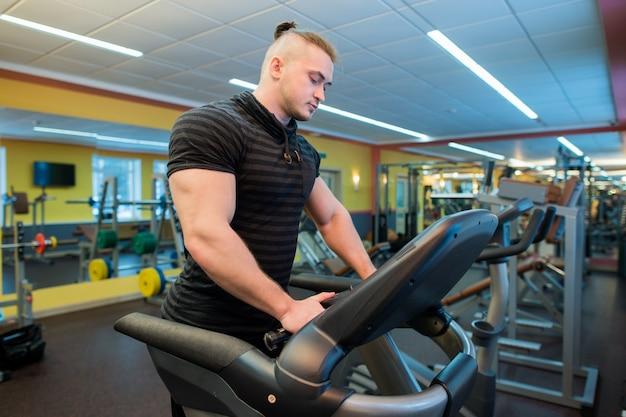 Attraktiver mann auf einem laufband im fitnessstudio