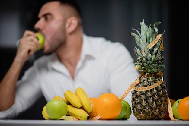 Attraktiver mann, der an einem tisch sitzt, auf dem frische frucht liegt. der typ, der einen apfel isst. das konzept eines gesunden lebensstils