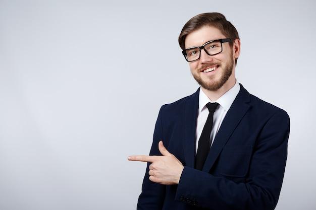 Attraktiver mann, der anzug und brillenwand, geschäftskonzept, kopierraum trägt, auf zeigt, verspottet.