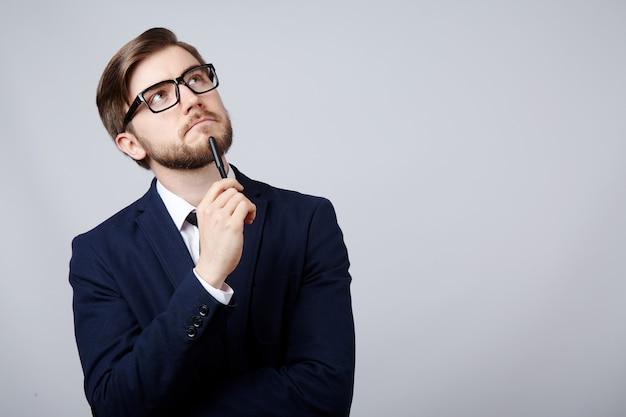 Attraktiver mann, der anzug- und brillenwanddenken, geschäftskonzept, kopierraum, porträt, haltepfanne trägt.