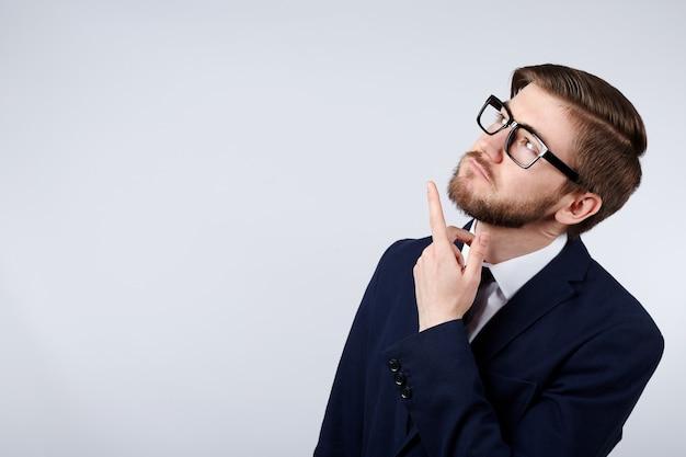 Attraktiver mann, der anzug- und brillenwanddenken, geschäftskonzept, kopierraum, porträt, modell trägt.