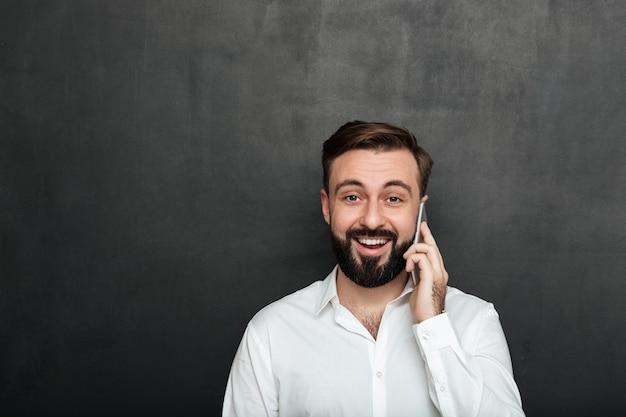Attraktiver mann, der auf dem smartphone hat das angenehme gespräch schaut auf kamera über graphitkopienraum spricht