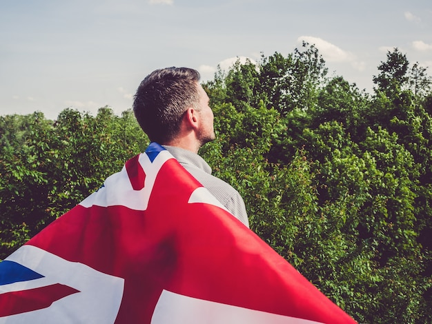 Attraktiver mann, der australische flagge hält. nationalfeiertag