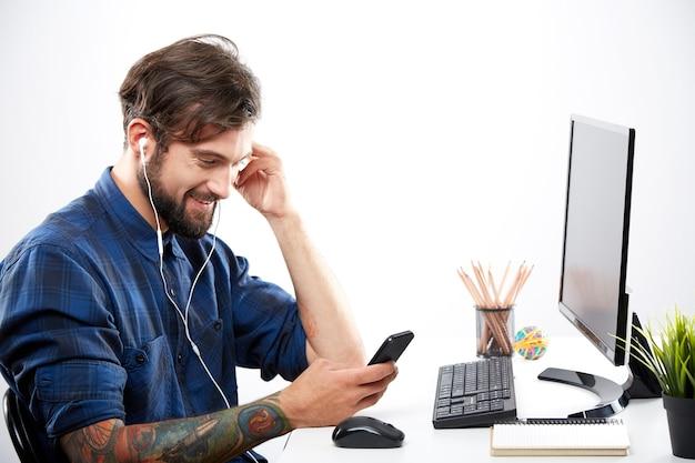 Attraktiver mann, der blaues hemd trägt, das mit laptop sitzt und zur musik, freiberufliches konzept, porträt, online-job, entspannung auflistet.
