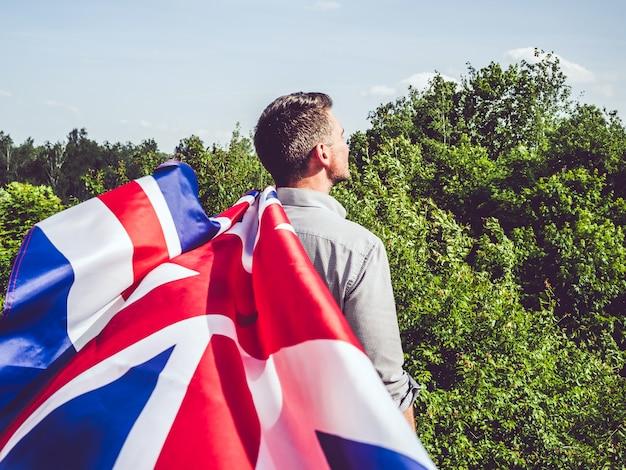 Attraktiver mann, der britische flagge, nahaufnahme hält