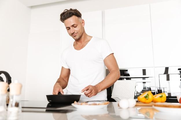 Attraktiver mann, der eier zum frühstück kocht