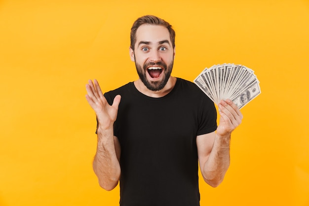 Attraktiver mann, der ein einfaches schwarzes t-shirt trägt und lächelt und geld bargeld isoliert über gelber wand hält?