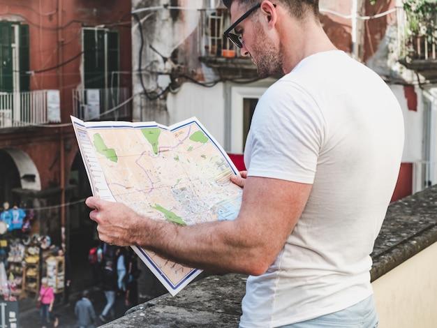 Attraktiver mann, der eine karte mit anblick betrachtet