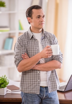 Attraktiver mann, der eine tasse tee hält und weg schaut.