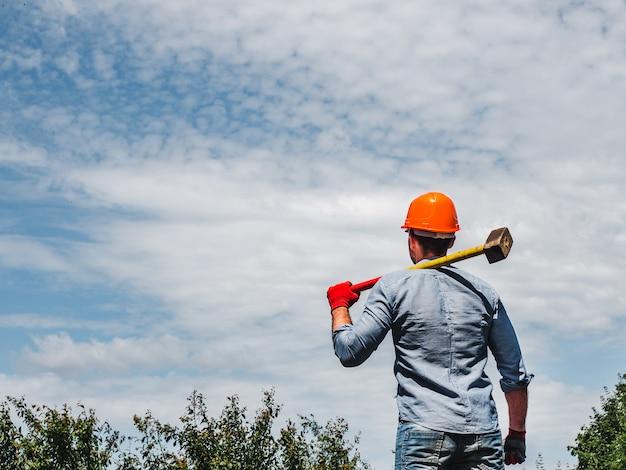 Attraktiver mann, der einen vorschlaghammer im park vor dem hintergrund der grünen bäume hält. nahansicht. konzept von arbeit und beschäftigung