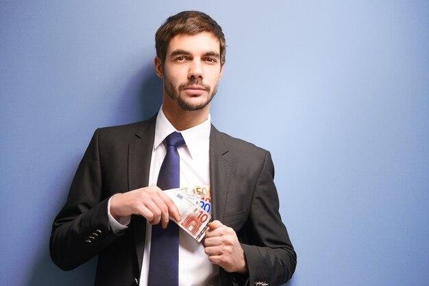 Attraktiver mann, der euro-banknoten im anzug auf blau versteckt