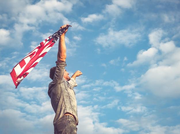 Attraktiver mann, der flagge der vereinigten staaten hält