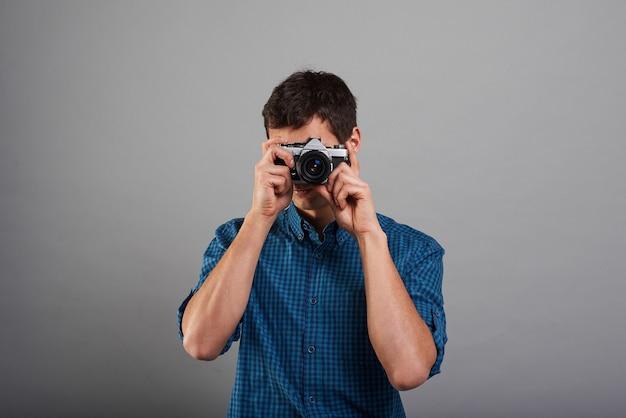 Attraktiver mann, der foto mit weinlesekamera macht