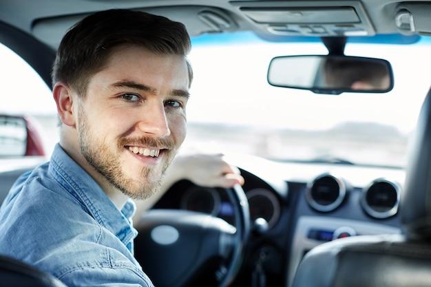 Attraktiver mann, der im automobil sitzt und kamera betrachtet und lächelt, neues auto kaufend.