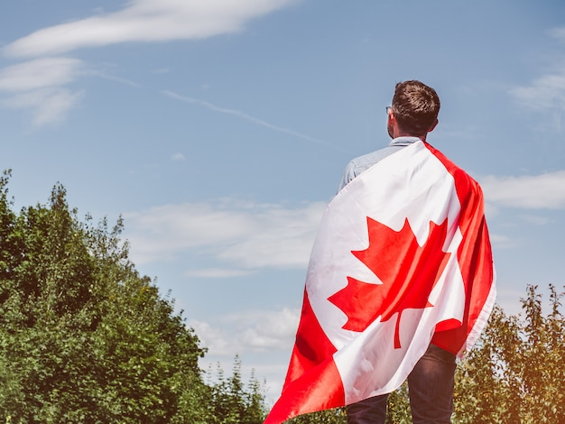 Attraktiver mann, der kanadische flagge hält. nationalfeiertag