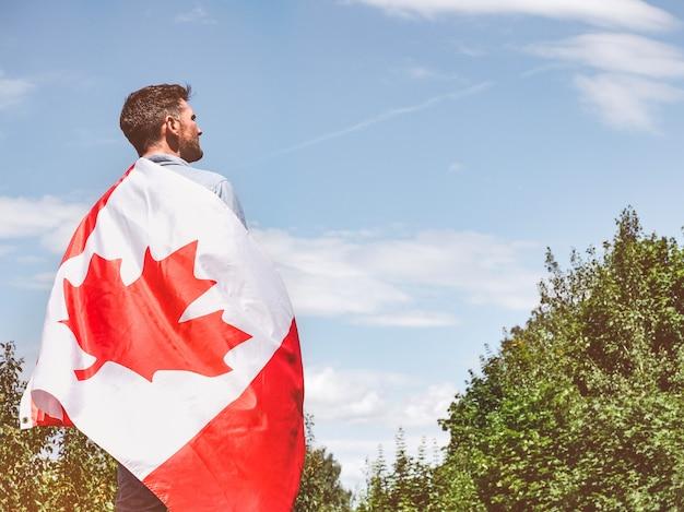 Attraktiver mann, der kanadische flagge über seinen schultern auf blauem himmelshintergrund hält