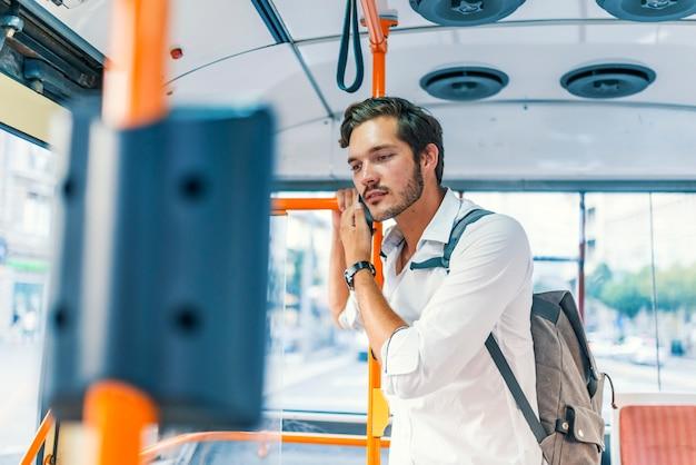 Attraktiver mann, der öffentlich am bus des telefons spricht