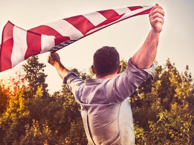 Attraktiver mann, der us-flagge hält. vorbereitungen für die feiertage