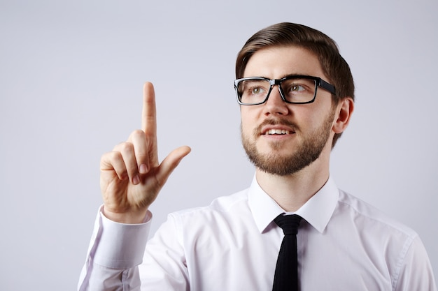 Attraktiver mann, der weiße hemd- und brillenwand, geschäftskonzept, kopienraum, porträt, eine idee tragend trägt.