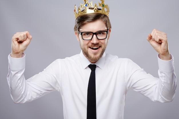 Attraktiver mann, der weißes hemd, krone und brillenwand, geschäftskonzept, kopienraum, porträt, glücklich trägt.