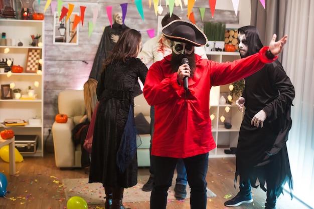 Attraktiver mann, der wie ein pirat verkleidet ist und karaoke auf der halloween-party mit seinen freunden macht.