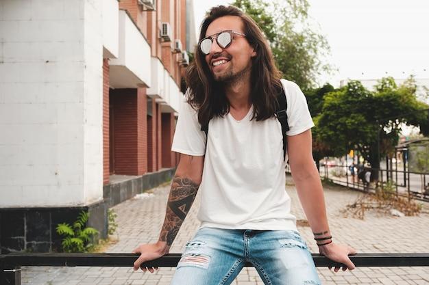 Attraktiver mann des porträts mit sonnenbrille auf dem städtischen szenenlächeln