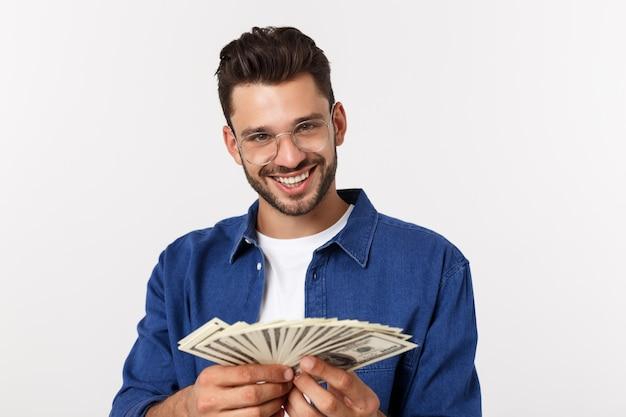 Attraktiver mann hält bargeld in einer hand, auf getrenntem weiß an